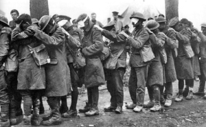 British soldiers temporarily blinded by gas attack await attention at a field-dressing station.