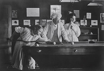 "Clemens/ Twain plays billiards with Louise Paine and Dorothy Harvey, two of his ""Angelfish"" in his Aquarium Club."