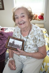 "Virginia ""Ginny"" Pfenninger, holding a picture of herself from her earlier days"